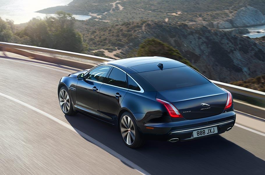 Jaguar XJ Heckansicht Seitenansicht Schwarz Berge Straße