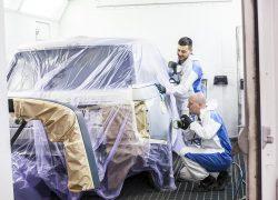 Team AUTO STAHL Wien 20 Lackierkabine Lackierarbeiten an einem Fahrzeug, Seitenansicht gemeinsames Arbeiten