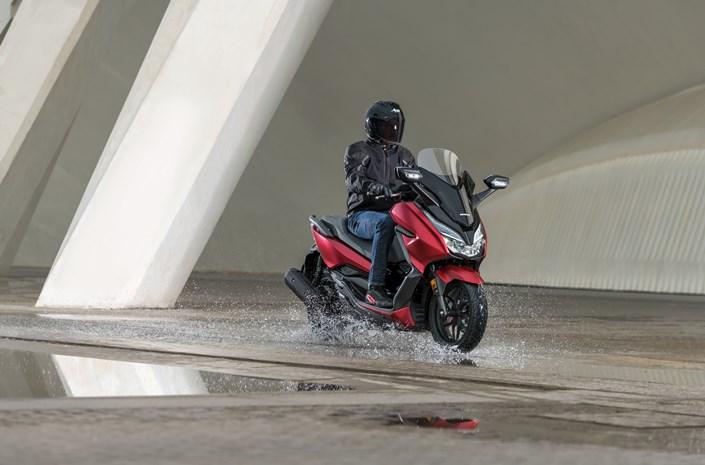 Honda Forza 125 bei Auto Stahl Seitenansicht Rot Schwarz Wasser