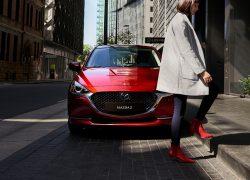 Mazda2 Modellabbildung in der Modellfarbe rot in Frontansicht mit vorbeigehender Frau