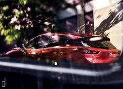 Mazda CX-3 Detail der Modellabbildung in schräger Frontansicht in moderner Umgebung, Modellfarbe rot