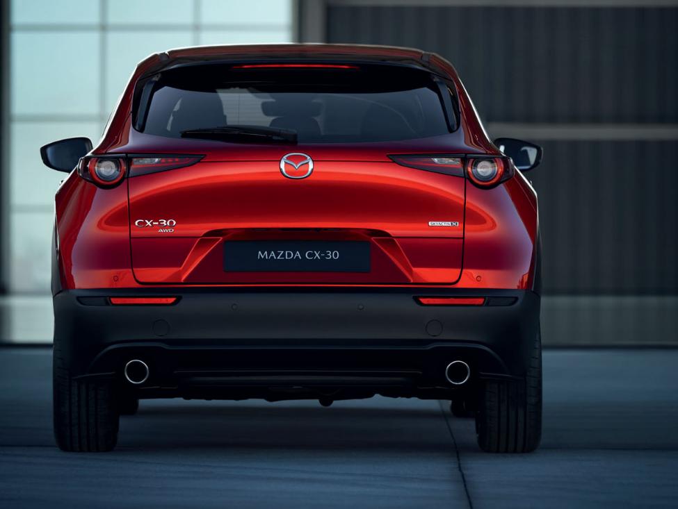 Mazda CX-30 Modellabbildung Heckansicht in moderner Umgebung, Modellfarbe rot