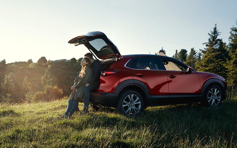 Mazda CX-30 Stimmungsbild, Mann und Frau am geöffneten Kofferraum lehnend