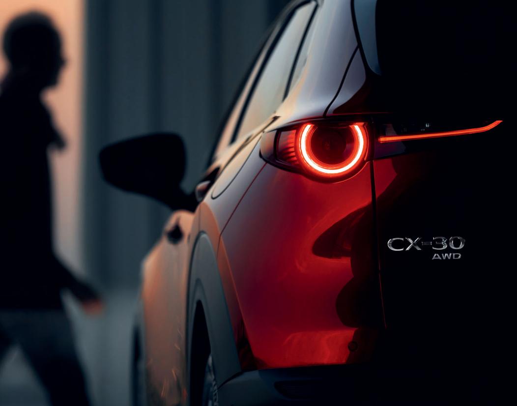 Mazda CX-30 Detail der Modellabbildung in Heckansicht in moderner Umgebung, Modellfarbe rot