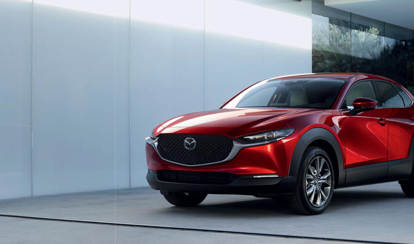 Mazda CX-30 Detail der Modellabbildung in schräger Frontansicht in moderner Umgebung, Modellfarbe rot