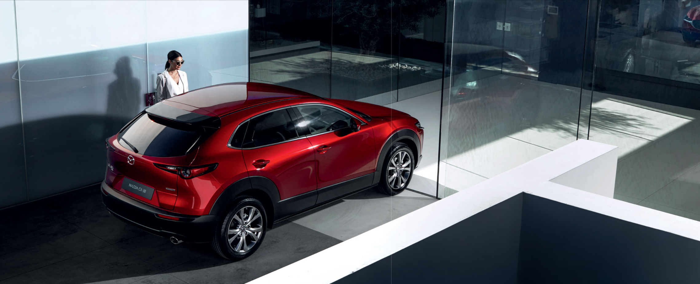 Mazda CX-30 Detail der Modellabbildung in schräger Heckansicht in moderner Umgebung, Modellfarbe rot