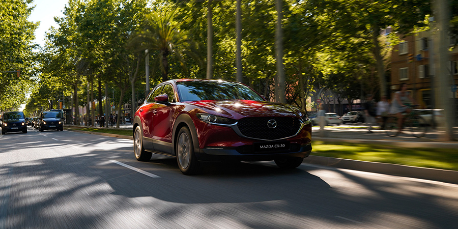 Mazda CX-30 Modellabbildung in Fahrt, Modellfarbe rot in urbaner Umgebung
