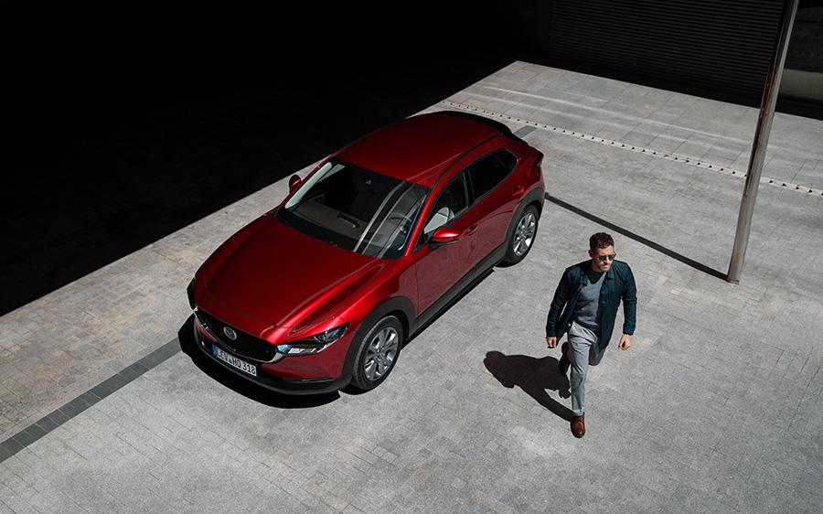 Mazda CX-30 Modellabbildung, Außenansicht mit modernem Fahrer, Wagenfarbe rot