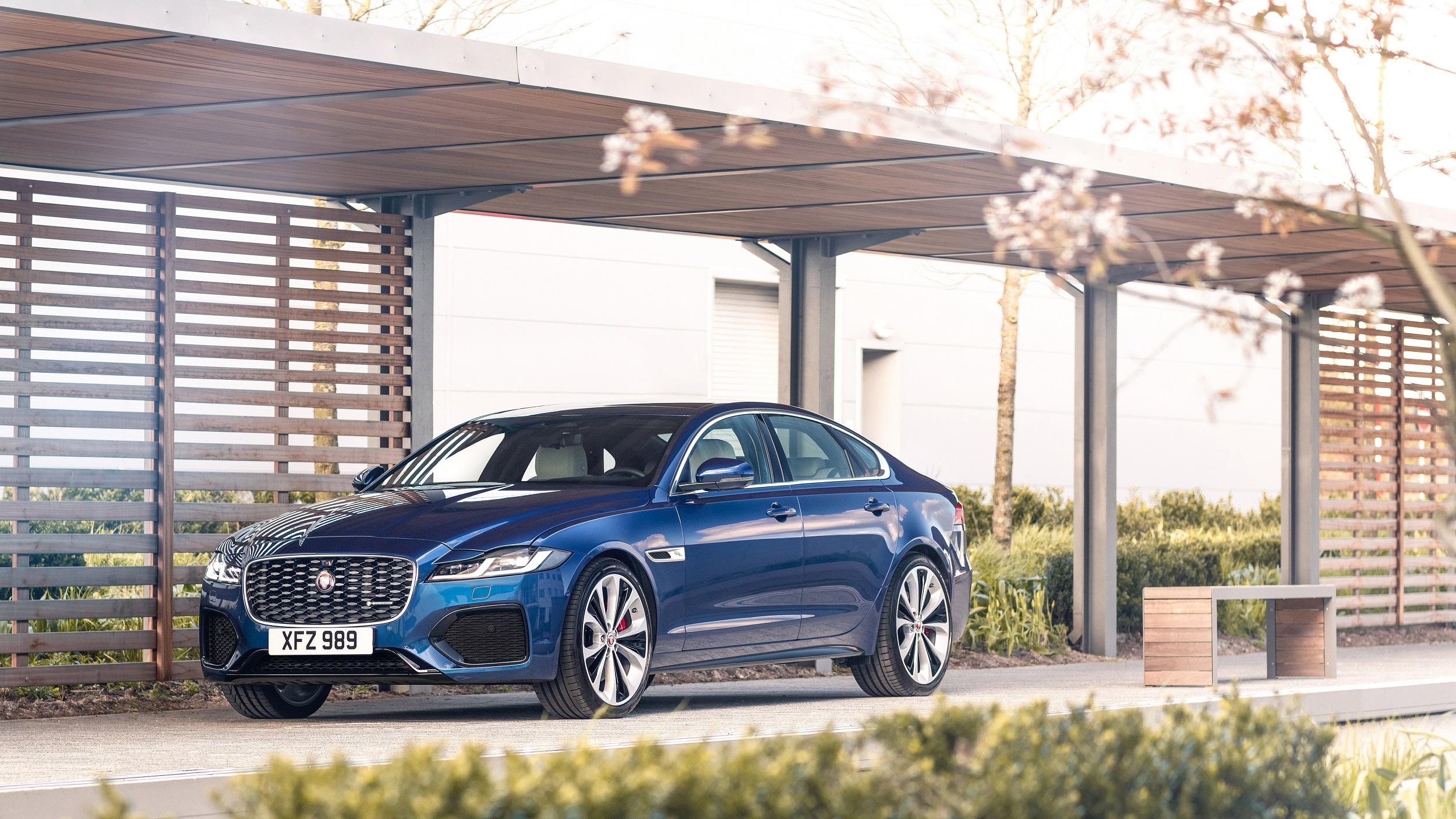 Jaguar XF in der Modellfarbe blau, Seitenansicht vor mordernem Haus
